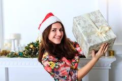 Muchacha sonriente hermosa que sostiene una caja con el regalo de la Navidad Imagen de archivo libre de regalías