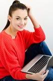 Muchacha sonriente hermosa que sostiene una computadora portátil. Imagenes de archivo