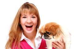Muchacha sonriente hermosa y pequeño perro. Foto de archivo