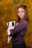Muchacha sonriente joven con el perrito blanco del bullterrier Imagen de archivo