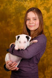 Muchacha sonriente joven con el perrito blanco del bullterrier Fotografía de archivo