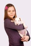 Muchacha sonriente joven con el perrito blanco del bullterrier Imágenes de archivo libres de regalías
