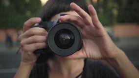 Muchacha sonriente joven con la cámara metrajes