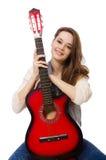 Muchacha sonriente joven con la guitarra aislada en blanco Fotografía de archivo libre de regalías