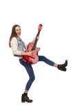 Muchacha sonriente joven con la guitarra aislada en blanco Foto de archivo