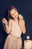 Muchacha sonriente joven con la magdalena Foto de archivo