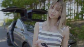 Muchacha sonriente joven con llaves del coche en su palma almacen de metraje de vídeo