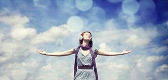 Muchacha sonriente joven con los auriculares en el fondo del cielo azul Imagenes de archivo