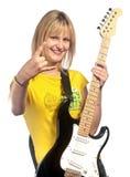 Muchacha sonriente joven con una guitarra eléctrica Fotos de archivo libres de regalías