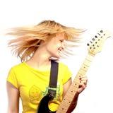 Muchacha sonriente joven con una guitarra eléctrica Fotografía de archivo