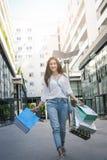Muchacha sonriente joven del adolescente que camina en la calle con los panieres Fotografía de archivo libre de regalías