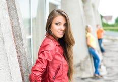 Muchacha sonriente joven en chaqueta roja Imagenes de archivo