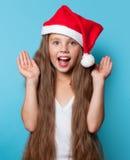 Muchacha sonriente joven en el sombrero de Santas Imagen de archivo
