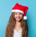 Muchacha sonriente joven en el sombrero de Santas Foto de archivo