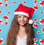 Muchacha sonriente joven en el sombrero de Santas Imagen de archivo libre de regalías