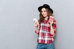 Muchacha sonriente joven en mensaje que manda un SMS de la camisa en el teléfono móvil Fotografía de archivo libre de regalías