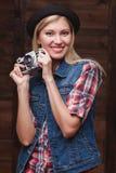 Muchacha sonriente joven en sombrero negro con la cámara del vintage Imagenes de archivo