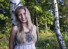 Muchacha sonriente joven en una arboleda del abedul imagenes de archivo