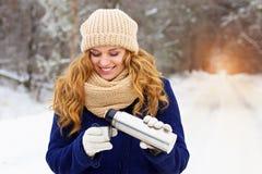 Muchacha sonriente joven hermosa en té de colada de la chaqueta azul del thermocup Muchacha del viaje imagenes de archivo
