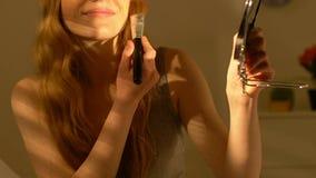 Muchacha sonriente joven que aplica el polvo de la piel, prepar?ndose para la fecha, extremidades del maquillaje almacen de metraje de vídeo