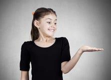 Muchacha sonriente joven que gesticula al espacio en la derecha Imagenes de archivo