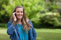 Muchacha sonriente joven que habla en el teléfono Imagen de archivo