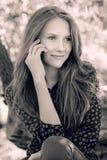 Muchacha sonriente joven que habla en el teléfono, foto blanco y negro Imágenes de archivo libres de regalías