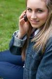 Muchacha sonriente joven que habla en el teléfono mientras que se sienta Imagenes de archivo