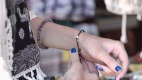 Muchacha sonriente joven que intenta las pulseras coloreadas en la tienda almacen de video