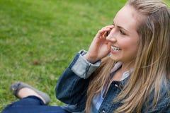 Muchacha sonriente joven que llama con su teléfono móvil mientras que se sienta en a Fotografía de archivo libre de regalías