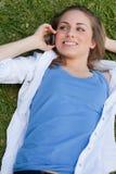 Muchacha sonriente joven que miente en ella detrás mientras que habla con su célula Foto de archivo libre de regalías
