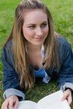 Muchacha sonriente joven que miente en la hierba y la lectura Fotos de archivo libres de regalías