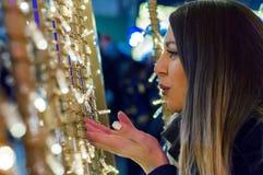 Muchacha sonriente joven que mira adelante a la Navidad que sopla un beso Fotos de archivo libres de regalías
