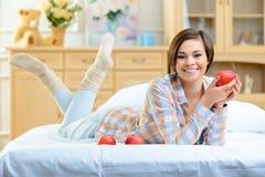 Muchacha sonriente joven que presenta con las manzanas Fotos de archivo