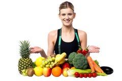 Muchacha sonriente joven que presenta las frutas frescas Imágenes de archivo libres de regalías