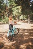 Muchacha sonriente joven que se coloca al lado de una bicicleta con un ramo de flores en el parque la mejor época de caminar con  Fotos de archivo