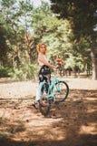 Muchacha sonriente joven que se coloca al lado de una bicicleta con un ramo de flores en el parque la mejor época de caminar con  Foto de archivo