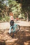 Muchacha sonriente joven que se coloca al lado de una bicicleta con un ramo de flores en el parque la mejor época de caminar con  Fotografía de archivo