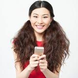 Muchacha sonriente joven que usa el teléfono celular imágenes de archivo libres de regalías