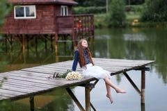 Muchacha sonriente linda con un ramo de margaritas en el embarcadero que sueñan descalzo Imagen de archivo