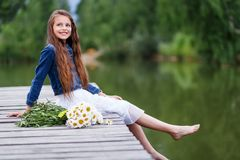 Muchacha sonriente linda con un ramo de margaritas en el embarcadero que sueñan descalzo Imágenes de archivo libres de regalías