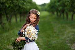 Muchacha sonriente linda con un ramo de margaritas y de una flor en el pelo muchacha con un manojo de manzanillas Imágenes de archivo libres de regalías