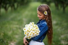 Muchacha sonriente linda con un ramo de margaritas y de una flor en el pelo muchacha con un manojo de manzanillas Foto de archivo libre de regalías