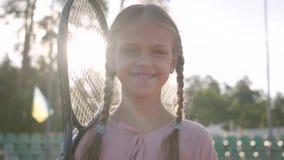 Muchacha sonriente linda del retrato pequeña con coletas y una estafa de tenis en su hombro que mira en la cámara que se coloca a metrajes
