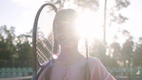 Muchacha sonriente linda del retrato pequeña con coletas y una estafa de tenis en su hombro que mira en la cámara que se coloca a almacen de metraje de vídeo