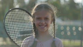 Muchacha sonriente linda del retrato pequeña con coletas y una estafa de tenis en su hombro que mira en la cámara que se coloca a almacen de video