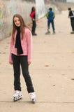 Muchacha sonriente linda en los rodillos afuera con los amigos Imagen de archivo libre de regalías
