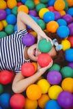 Muchacha sonriente linda en piscina de la bola de la esponja fotografía de archivo