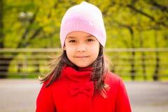 Muchacha sonriente linda en sombrero rosado en la capa roja que mira la cámara Imagenes de archivo