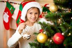 Muchacha sonriente linda que adorna el árbol de navidad con las bolas de oro Imagen de archivo